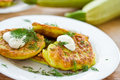 Zucchini pancakes on a plate with greens Stock Images