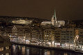 Zurich centre by night the river limmat with the university and church on the background during a winter on the foreground the Stock Photo