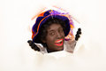 Zwarte piet sinterklaas black pete looking through hole typical dutch character part of a traditional event celebrating the Stock Photo