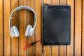 Zwarte tabletpc en witte hoofdtelefoons op de houten achtergrond Royalty-vrije Stock Foto's