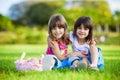 Zwei junge lächelnde Mädchen, die im Gras umarmen Stockbild