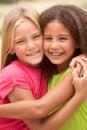 Zwei Mädchen im Park, der Umarmung sich gibt Stockfotografie