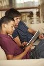 Zwei teenager die auf sofa at home using tablet computer und laptop sitzen Lizenzfreie Stockfotografie