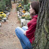 Woman at cemetery. Sad young woman mourning at cemetery; profile view Stock Photo