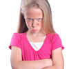 Angry little girl. Portrait of a pretty little Caucasian preteen girl child with angry facial expression and crossed arms in front of her having a tantrum. Image Stock Photo
