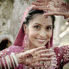 Young beautiful Indian Hindu bride standing under tree with painted hands raised. To her face Stock Photo