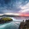 Landscape of Iceland with Godafoss waterfall. Godafoss waterfall. Beautiful landscape in Iceland. Man in red jacket standing on the rock and looking at the dawn Stock Photo