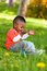 Stock Image : Υπαίθριο πορτρέτο μιας χαριτωμένης νεολαίας λίγο μαύρο αγόρι που παίζει με