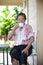 Stock Image :  Женское старшее усаживание в домашней террасе и выпивая горячем напитке