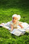 Stock Image : Adorable baby girl lying on green summer lawn