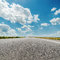 Stock Image : Asphalt road and clouds over it