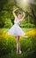 Stock Image :  Atrakcyjna dziewczyna w bielu skrótu smokingowy pozować blisko drzewnej huśtawki z kwiaciastą łąką w tle blond kobiety young
