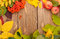 Stock Image : Autumn leaves, rowan berries and apples over wood background
