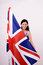 Stock Image : Beautiful British girl smiling holding up the UK flag looking away.
