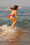 Stock Image : Beautiful girl jumping in the waves on the beach