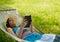Stock Image : Beautiful woman reading & relaxing in hammock
