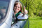 Stock Image : Beautiful young woman with thumbs up in her new car