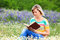 Stock Image : Blonde girl reading the flowery meadow.