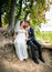 Stock Image : Bride and groom sitting under tree at river bank and kissing