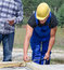 Stock Image : Builder measuring a wooden beam