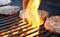 Stock Image : Burgers Cooking Over Flames On The Grill