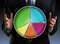 Stock Image : Businessman holding a colorful pie chart