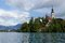 Stock Image : Church on an island on Bled lake with mountains and resort on the background