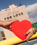 Stock Image : Couple holding red heart in front of love sign