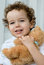 Stock Image : Curly-haired boy with teddy bear