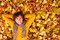 Stock Image : Curly man in yellow sweater and scarf lie on autumn leaves