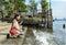 Stock Image : A cute Asian girl kneeling near the riverside dock