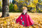 Stock Image : Cute child girl playing with fallen leaves in autumn