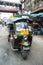 Stock Image : Famous three-wheeled taxi (tuktuk) parking at the street