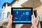 Stock Image : Female hands hold a tablet with system smart house on the backgr