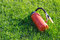 Stock Image : Fire extinguisher laying on green grass