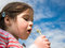 Stock Image : Girl blowing a dandelion against a blue sky