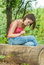 Stock Image : Girl outdoors in woods sitting on log