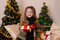 Stock Image : Girl with red giftbox over golden Christmas tree
