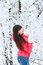 Stock Image : A girl stands near the snow-covered trees look upwards