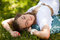 Stock Image : Girl wearing white dress out in the park lying on the grass