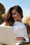 Stock Image : Girl in white dress lying on hay with laptop
