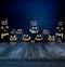 Stock Image : Halloween pumpkins in a dark background and wood floor