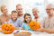 Stock Image : Happy family sitting with pumpkins at home