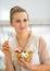Stock Image : Happy young housewife eating fresh fruit salad