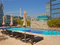 Stock Image : Hotel Rooftop Swimming Pool with deckchair & Buildings
