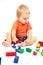 Little boy in an orange shirt is played Lego