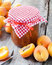 Stock Image : Jar of jam and ripe apricot fruits on table