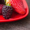 Stock Image : Juicy strawberry and blackberry in red plate on a wooden sur