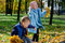 Stock Image : Laughing children playing with fall leaves