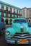 Stock Image : Light green vintage taxi car of Cuba in front of old building in Havana